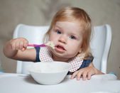 Little girl eating porridge — Stock Photo