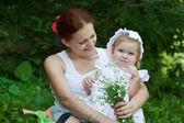 Mother holding a baby in a park — Stock Photo