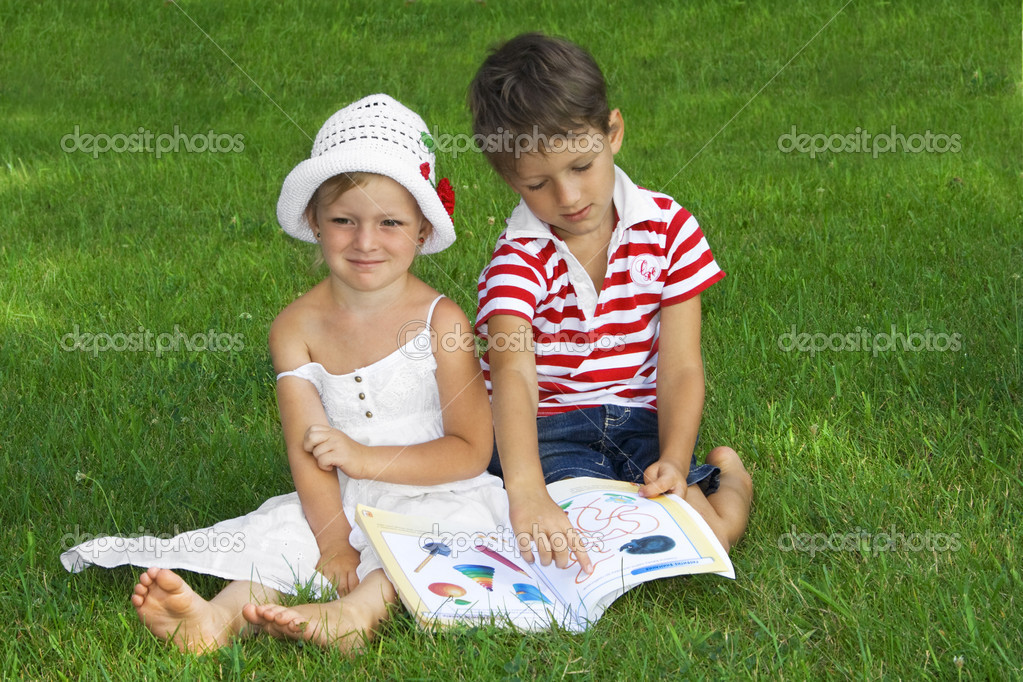 Children in the park reading a book — Stock Photo #6181019