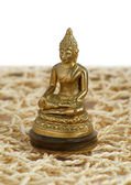 Bronze Buddha in a lotus position on the mat — Stock Photo