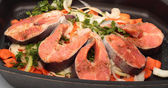 Salmon steaks with vegetables on the cook griddle — Stock Photo