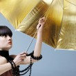 Royalty-Free Stock Photo: Woman with gold umbrella.
