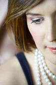Beautiful young woman with natural make-up and brown hair wearing pearls — Stock Photo
