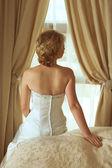 Beautiful blond bride in satin pearl dress. — Stock Photo