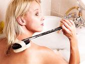 Mladá žena mytí ji zpět — Stock fotografie