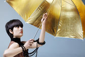 Woman with gold umbrella. — Stock Photo