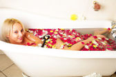 Blond woman in rose petal bath with smile — Stock Photo