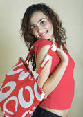 Beautiful young woman with red bag. — Stock Photo
