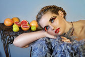 Beautiful woman with feathers and fruit. — Stock Photo