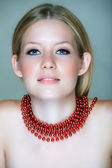 Blond woman with red beads — Stock Photo