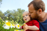 Father in early thirties gives his son a kiss — Stock Photo