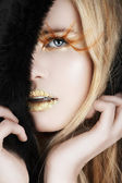 Gold leaf and false eyelashes on a blond woman. — Stock Photo