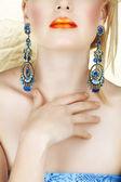 Orange lips and blue earings. — Stock Photo