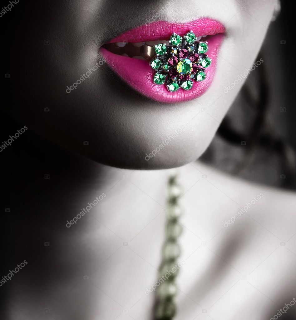 Young woman holding a precious green stones ring in her pink lips  — Stock Photo #5396408