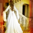 Stock Photo: Beautiful bride in long silk coat on staircase