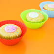 Three vanilla muffins in plastic cups - Foto Stock