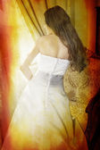 Beautiful bride with long curly hair in silk dress on grunge background.Bea — Stock Photo
