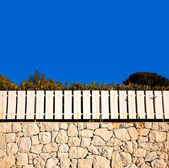 White fence on stone wall — Stock Photo