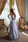 Beautiful bride next to windows — Stock Photo