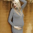 Pregnant blonde woman at the wall — Stock Photo