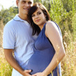 Man and pregnant wife in field — Stock Photo