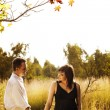 Pregnant woman and husband outdoors - Stock Photo