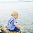 Little blond one year old boy sitting on a rock — Stock Photo