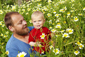 Father and baby boy in flower field — Stock Photo