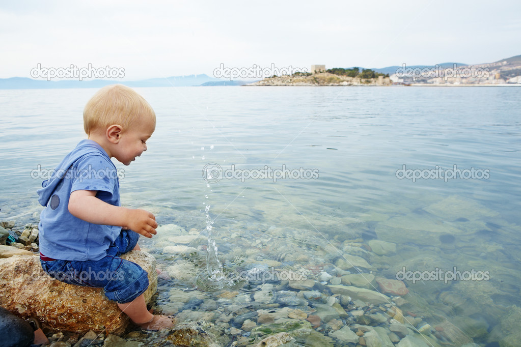 Little blond one year old boy sitting on a rock with his feet in the sea water on a warm summer evening and watching stones make splashes, in a resort town in T  Stock Photo #6123843