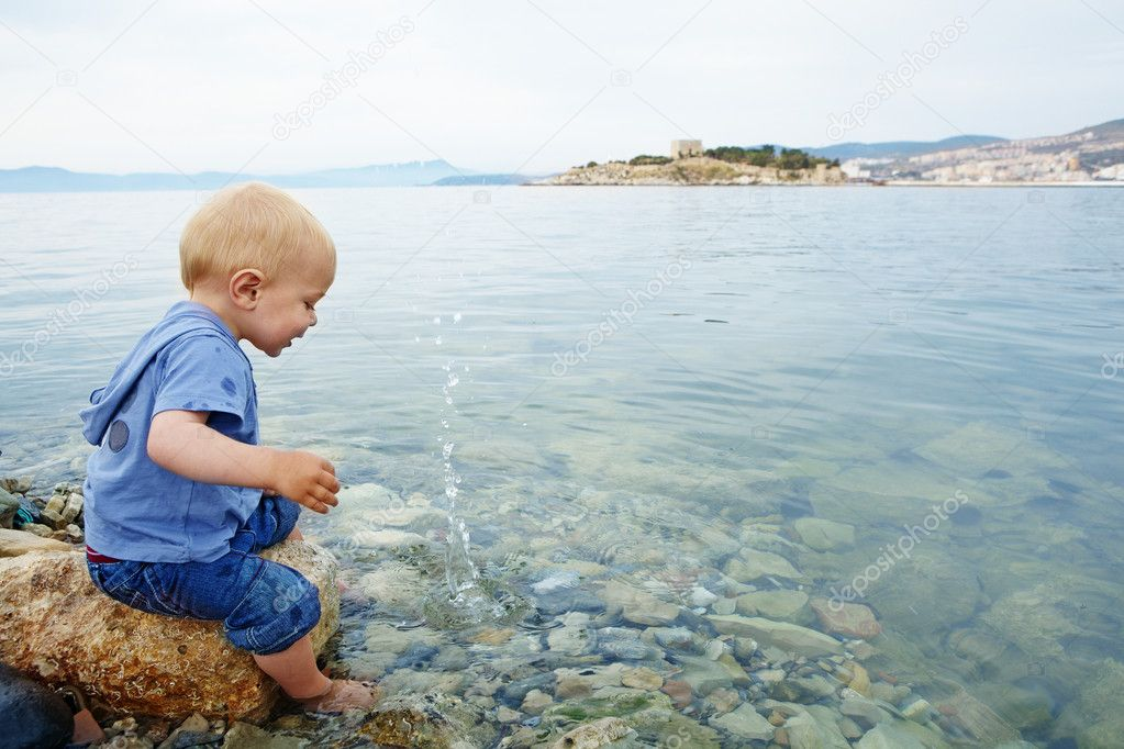 Little blond one year old boy sitting on a rock with his feet in the sea water on a warm summer evening and watching stones make splashes, in a resort town in T   #6123843