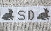 Easter bunny Cross-stitch on cotton blanket. — Stock Photo