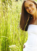 Young teenage woman in grass — Stock Photo