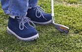 Chaussures garçon et club de golf sur l'herbe — Photo
