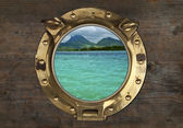 Antique Porthole with Tropical View on a wooden Wall Background. — Stock Photo