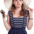 Stock Photo: A girl in a straw hat with sunglasses in hand