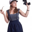 A girl in a sailor cap holding a pair of binoculars and a pipe for smoking — Stock Photo