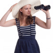 A girl in a big straw hat looking through binoculars — Stock Photo