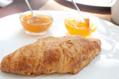 Large croissant on a plate with a portion of jam — Stock Photo