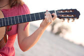 A girl in a dress playing a guitar — Stock Photo