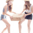 Two girls in straw hats with a straw suitcase — Stock Photo