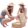 Two girls in straw hats with a straw suitcase, studio photography — Stock Photo