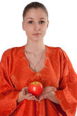 Girl in orange dress offers a red apple — Stock Photo