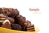 Chocolate candy on yellow plate — Stock Photo