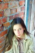 Sad girl near brick wall — Stock Photo