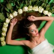 Girl lay among the flowers of roses — Stock Photo