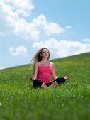 Vrouw zitten op het gras — Stockfoto