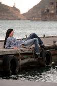 Mulher deitada em um píer no fundo do mar — Fotografia Stock
