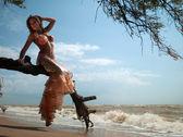 žena v exotické šaty sedí na větvi — Stock fotografie