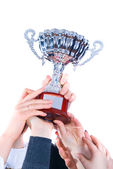 Prize-winning cup in hands of a command — Stock Photo