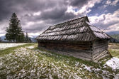 Snowy abandoned wooden house in the spring mountains — Foto de Stock